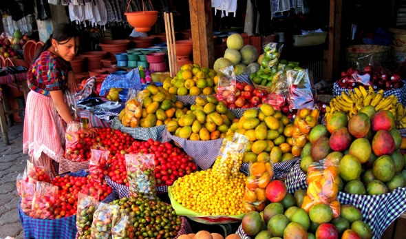 A young women prepares her fruit stand for the day in Antigua, Guatemala.